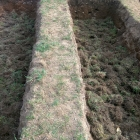 Dno záhonu jsme pokryli vrstvou drnů. Pokládali jsme je trávou směrem dolů, kořínky nahoru.